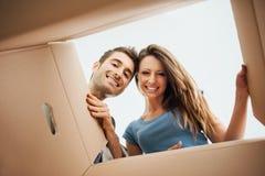 Couples heureux ouvrant une boîte images stock