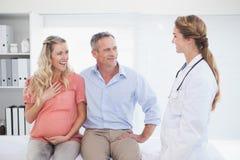 Couples heureux parlant au docteur image stock