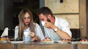 Couples heureux partageant le contenu de media sur la ligne chacun avec son téléphone intelligent dans un café banque de vidéos