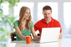 Couples heureux passant en revue sur l'ordinateur Photographie stock