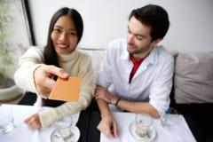 Couples heureux payant le repas avec la carte au restaurant photo stock