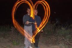 Couples heureux peignant les flammes de coeur du feu comme symbole de l'amour Images stock