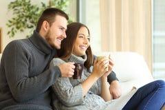 Couples heureux pensant et tenant les boissons chaudes en hiver Photo stock