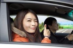 Couples heureux pilotant dans le véhicule Photos libres de droits
