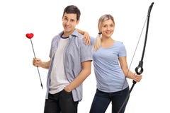 Couples heureux posant avec une flèche d'amour et un arc Images libres de droits