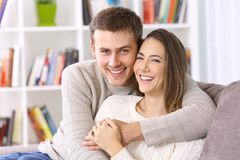 Couples heureux posant ensemble sur un divan à la maison photo stock