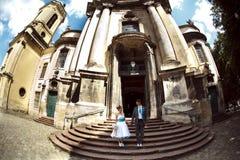 Couples heureux posant sur la vieille église de fond Image libre de droits