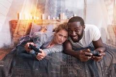 Couples heureux positifs se trouvant sur le lit Photos libres de droits