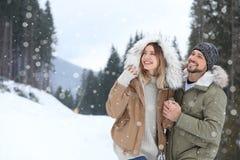 Couples heureux près de forêt de conifère le jour neigeux photo stock