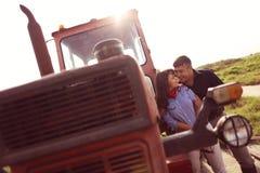 Couples heureux près de tracteur à la ferme Image libre de droits