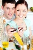 Couples heureux préparant des spaghetti et buvant du vin Images libres de droits