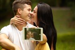Couples heureux prenant l'autoportrait au parc Tablette de Digitals Photo stock