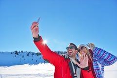 Couples heureux prenant la photo avec le bâton de selfie de smartphone dessus au-dessus du fond d'hiver Images libres de droits