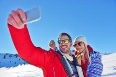 Couples heureux prenant la photo avec le bâton de selfie de smartphone dessus au-dessus du fond d'hiver Photos stock
