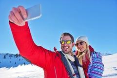 Couples heureux prenant la photo avec le bâton de selfie de smartphone dessus au-dessus du fond d'hiver Photographie stock libre de droits