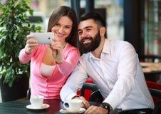 Couples heureux prenant la photo avec le téléphone portable en café Image stock