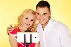 Couples heureux prenant la photo de selfie avec le bâton de selfie Image libre de droits