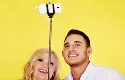Couples heureux prenant la photo de selfie avec le bâton de selfie Photos libres de droits