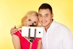 Couples heureux prenant la photo de selfie avec le bâton de selfie Photo stock