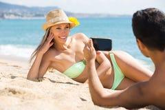Couples heureux prenant la photo sur la plage Images libres de droits