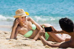 Couples heureux prenant la photo sur la plage Photo libre de droits