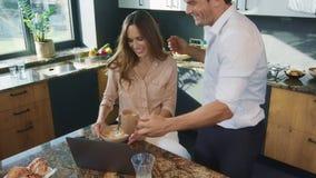 Couples heureux prenant le petit déjeuner à la cuisine Mari préparant la nourriture pour l'épouse occupée banque de vidéos