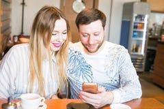Couples heureux prenant le petit déjeuner et se photographiant - jolis amants dans un restaurant regardant vers le bas le télépho Photo stock