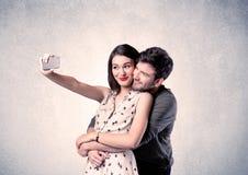 Couples heureux prenant le selfie avec le mur clair Photo libre de droits