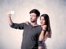 Couples heureux prenant le selfie avec le mur clair Photos libres de droits