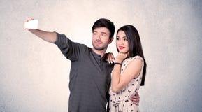 Couples heureux prenant le selfie avec le mur clair Images stock