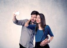 Couples heureux prenant le selfie avec le mur clair Photographie stock libre de droits