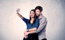 Couples heureux prenant le selfie avec le mur clair Image stock