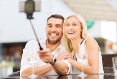 Couples heureux prenant le selfie avec le smartphone au café Images libres de droits