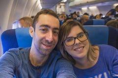 Couples heureux prenant le selfie avec le smartphone ou l'appareil-photo à l'intérieur de l'airp Photo libre de droits