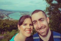 Couples heureux prenant le selfie avec le smartphone ou l'appareil-photo au-dessus de Budape Images stock