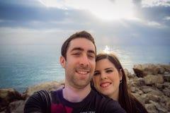 Couples heureux prenant le selfie avec le smartphone ou l'appareil-photo au-dessus du coucher du soleil Images stock