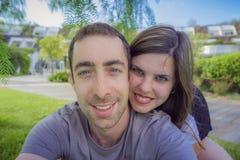 Couples heureux prenant le selfie avec le smartphone ou l'appareil-photo en parc Photo libre de droits