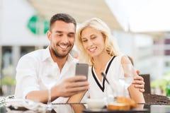 Couples heureux prenant le selfie avec le smatphone au café Image stock