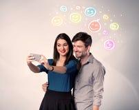 Couples heureux prenant le selfie avec le smiley Image stock