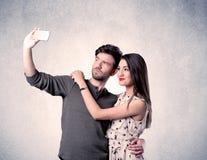 Couples heureux prenant le selfie avec le mur clair Images libres de droits