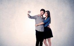 Couples heureux prenant le selfie avec le mur clair Image libre de droits