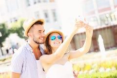 Couples heureux prenant le selfie en parc Image libre de droits