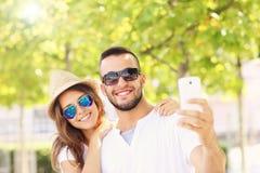 Couples heureux prenant le selfie en parc Images libres de droits