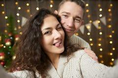 Couples heureux prenant le selfie et ayant l'amusement dans la décoration de Noël Intérieur en bois foncé avec des lumières Escro Image stock