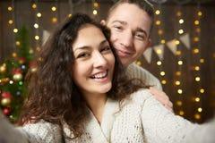 Couples heureux prenant le selfie et ayant l'amusement dans la décoration de Noël Intérieur en bois foncé avec des lumières Escro Photographie stock libre de droits