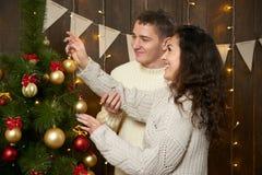 Couples heureux prenant le selfie et ayant l'amusement dans la décoration de Noël Intérieur en bois foncé avec des lumières Escro Images stock