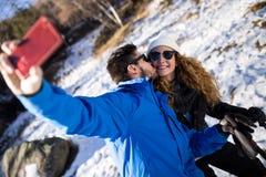 Couples heureux prenant le selfie par le smartphone au-dessus du fond d'hiver Photographie stock libre de droits
