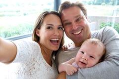 Couples heureux prenant un selfie avec le bébé images stock