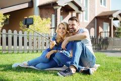 Couples heureux prenant un selfie sur le pique-nique d'arrière-cour Photographie stock libre de droits