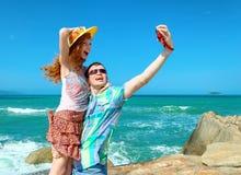 Couples heureux prenant une photo des vacances d'une plage image stock